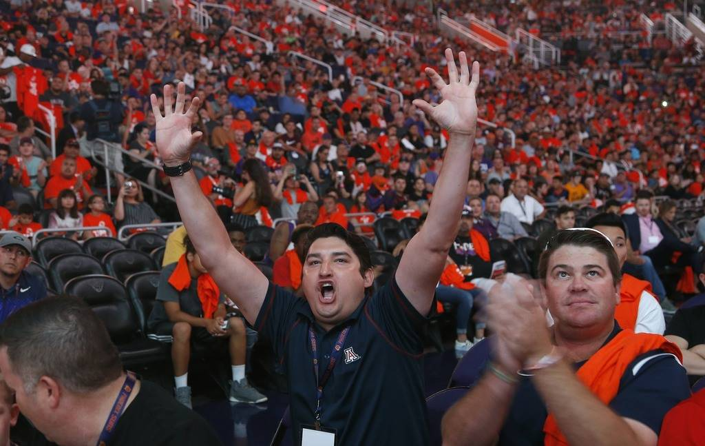 Phoenix Suns fan Ryan Maese, middle, cheers along with thousands of Suns fans in Phoenix as the Suns picked Deandre Ayton as the first selection in the NBA basketball draft Thursday, June 21, 2018 ...