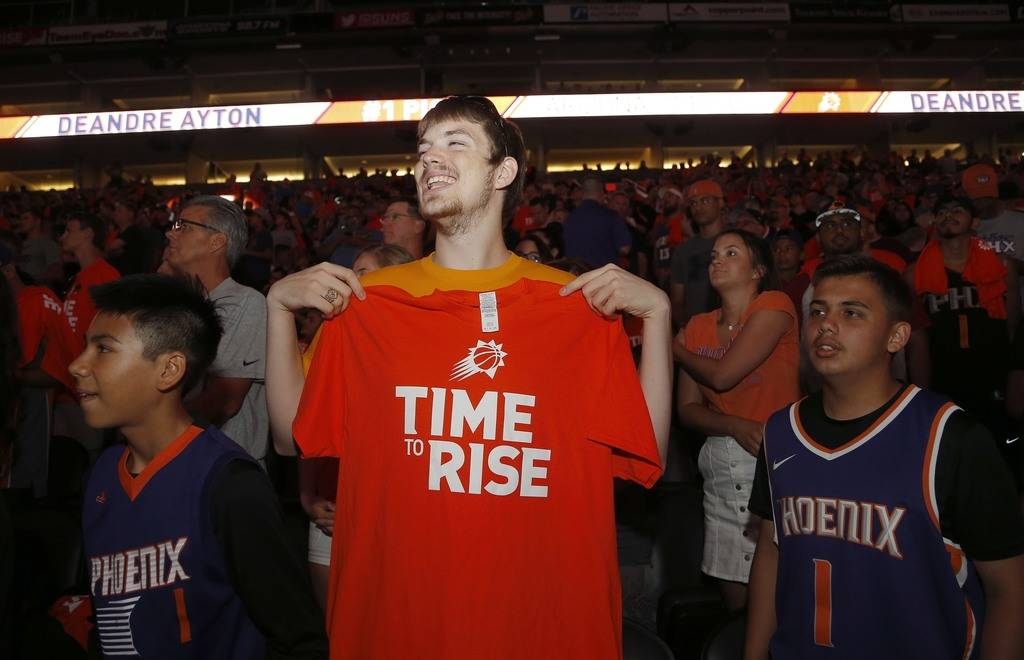 Phoenix Suns fans in Phoenix listen to the live broadcast as the Suns picked Deandre Ayton as the first selection in the NBA basketball draft Thursday, June 21, 2018, in Phoenix. (AP Photo/Ross D. ...