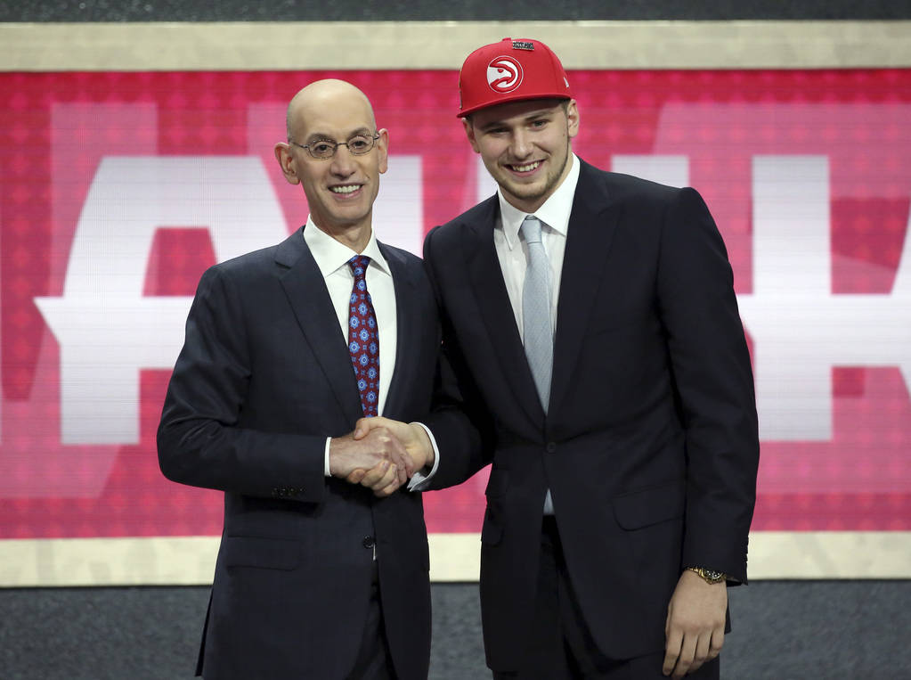 Luka Doncic, who plays for Real Madrid, poses for a picture with NBA Commissioner Adam Silver after Doncic was picked third overall by the Atlanta Hawks during the NBA basketball draft in New York ...