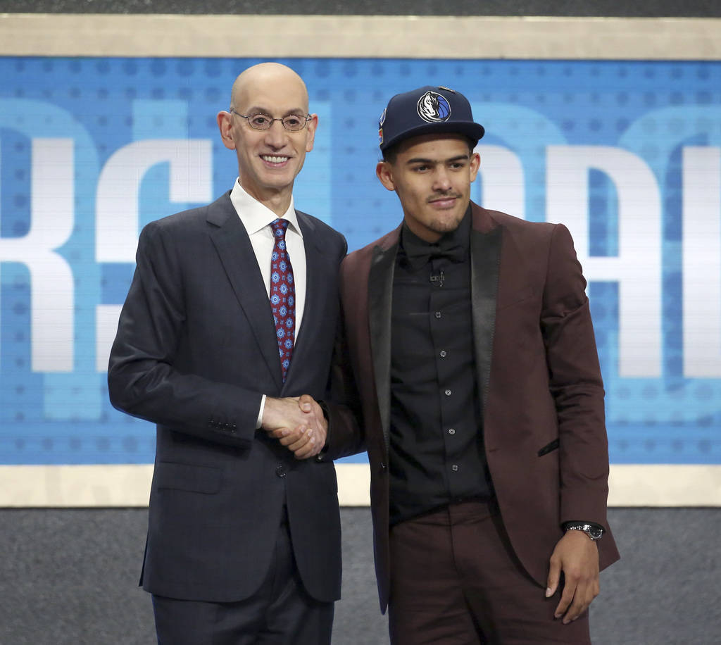 Oklahoma's Trae Young, right, poses with NBA Commissioner Adam Silver after he was picked fifth overall by the Dallas Mavericks during the NBA basketball draft in New York, Thursday, June 21, 2018 ...