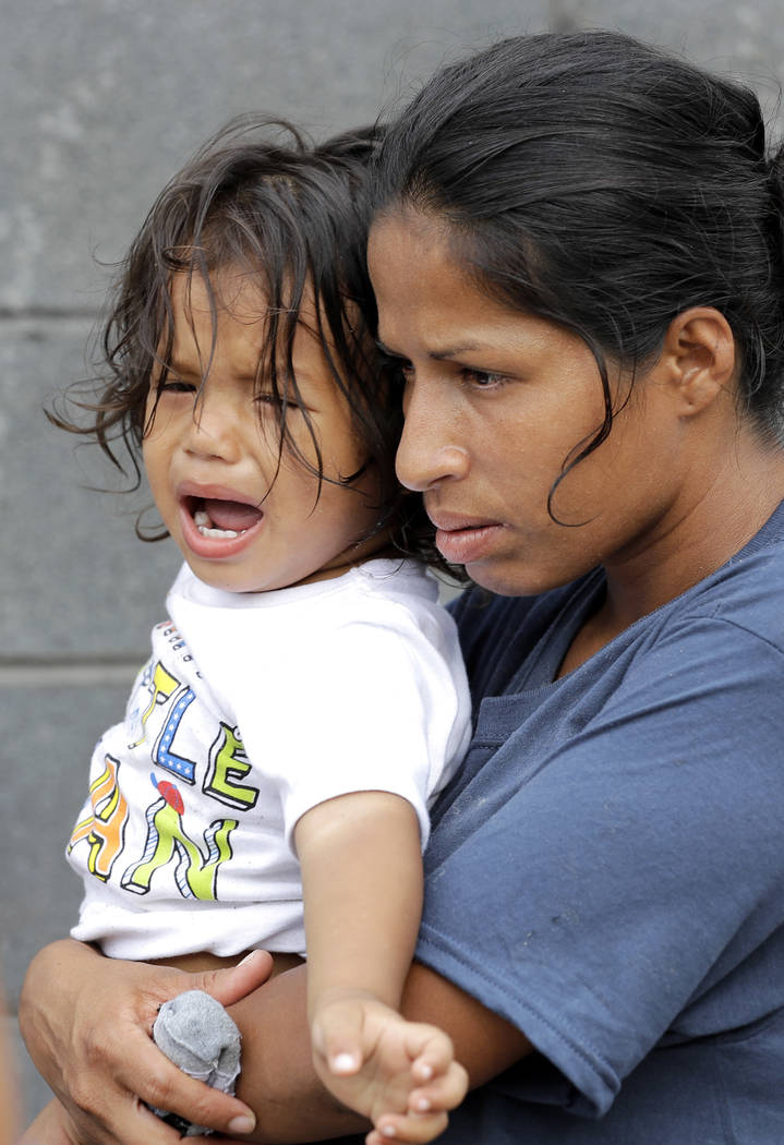 Jesus Funes, 19-months-old, cries as his mother, Diva Funes, both immigrants from Honduras, holds him after being escorted back to Reynosa, Mexico, Thursday, June 21, 2018. The family, who was see ...