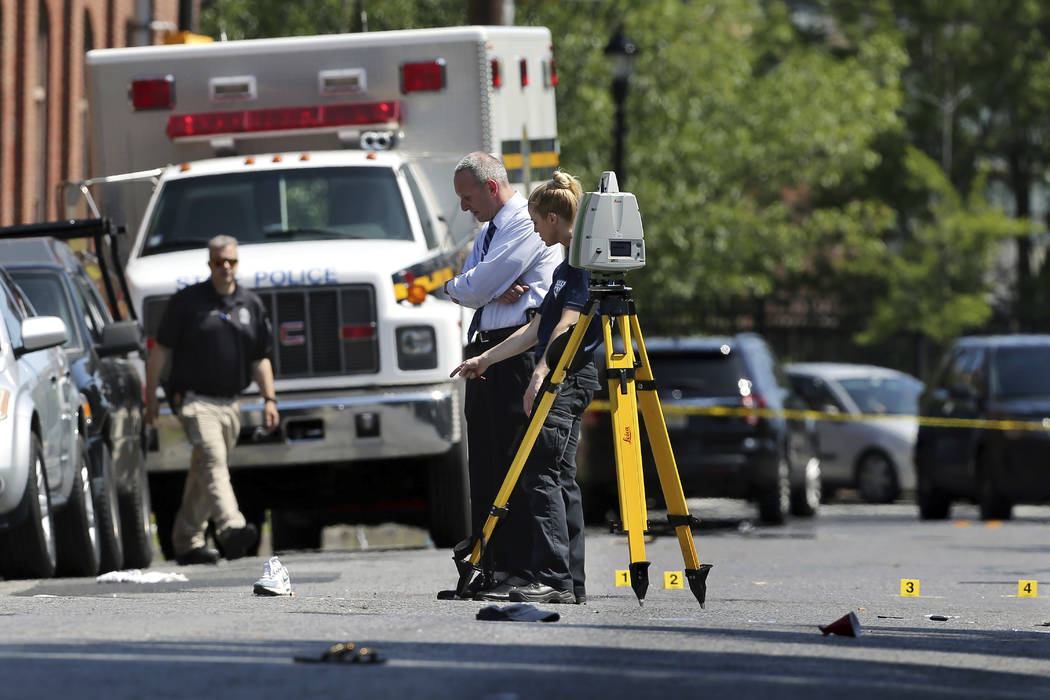 Investigators stand in a street near evidence markers outside the warehouse building where the Art All Night Trenton 2018 festival that was the scene of a shooting that resulted in numerous injuri ...