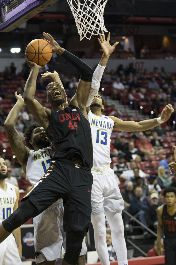 UNLV Rebels forward Brandon McCoy (44) goes up for a shot under pressure from Nevada Wolf Pack forward Elijah Foster (12) and guard Hallice Cooke (13) in the first half of the Mountain West Confer ...