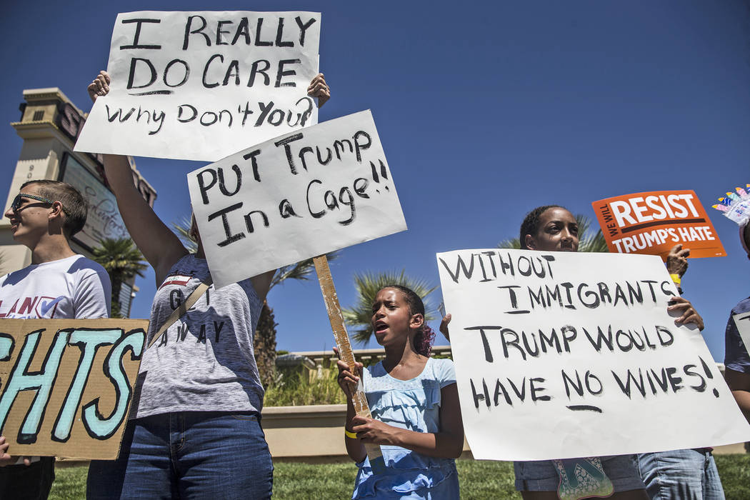 "Paige Faggins, middle, protests outside Suncoast hotel-casino ahead of President Donald Trump's appearance on Saturday, June 23, 2018, in Las Vegas. ""I'm here because Trump is separating fami ..."