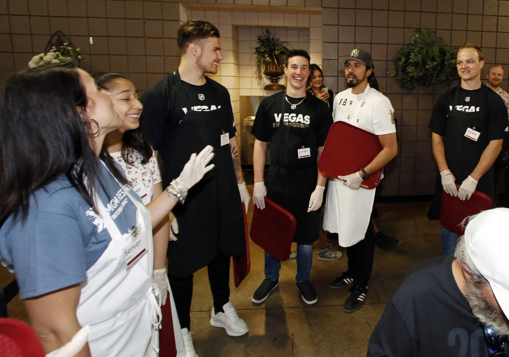 Volunteers and the Vegas Knight prospects Martin Bodak, third left, Rafael Harvey-Pinard, center, and Reid Duke, right, prepare to serve a special free community meal to clients at Catholic Charit ...