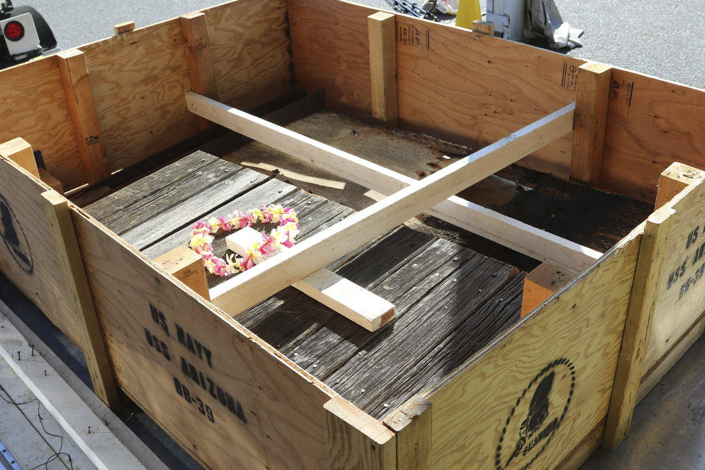 Part of a steel plate and wood deck from the USS Arizona, held in place by white beams, sits in a crate while waiting to be loaded onto an airplane Thursday, June 21, 2018 in Honolulu. (AP Photo/A ...
