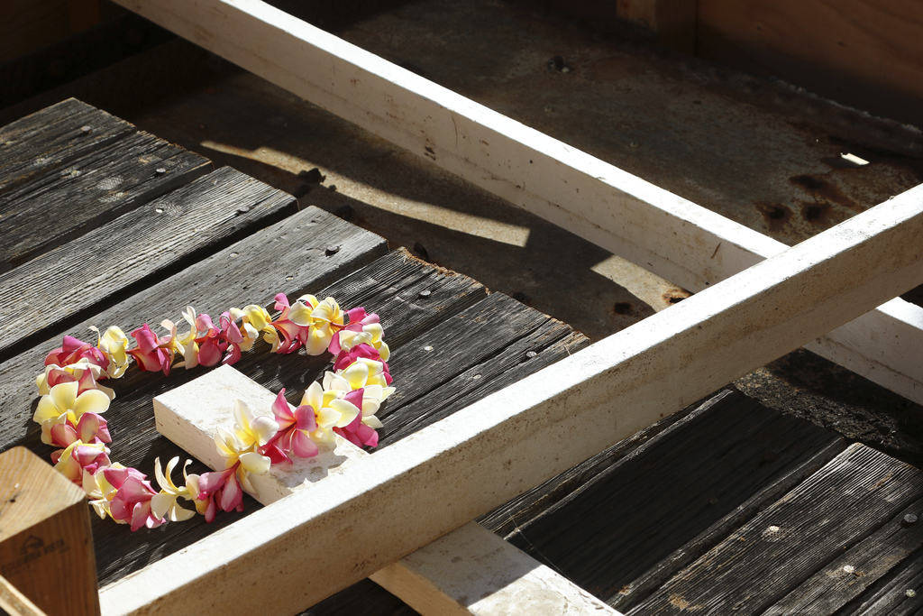 A flower lei sits on part of a wood deck and steel plate from the USS Arizona that are being held in place by white beams while sitting in a crate while waiting to be loaded onto a airplane Thursd ...