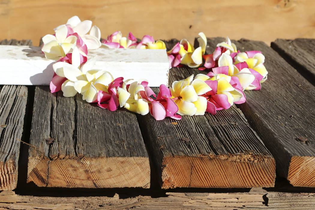 A flower lei sits on part of a wood deck from the USS Arizona, which is being held in place by white beams as it sits in a crate while waiting to be loaded onto an airplane Thursday, June 21, 2018 ...