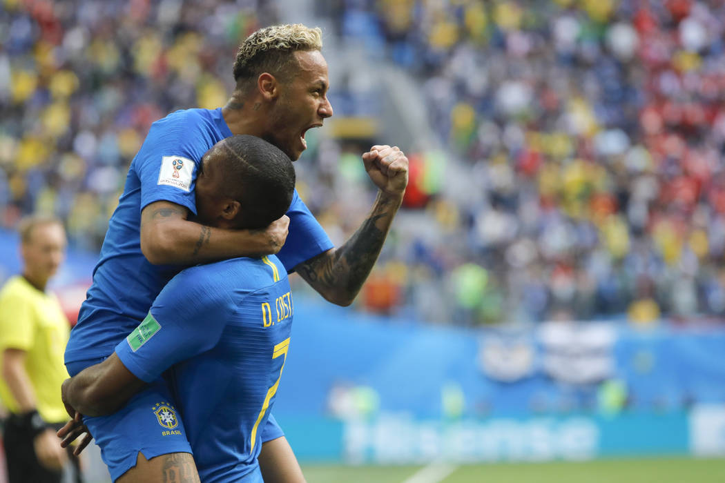 Brazil's Neymar, top, celebrates with teammate Douglas Costa after scoring his side's second goal during the group E match between Brazil and Costa Rica at the 2018 soccer World Cup in the St. Pet ...