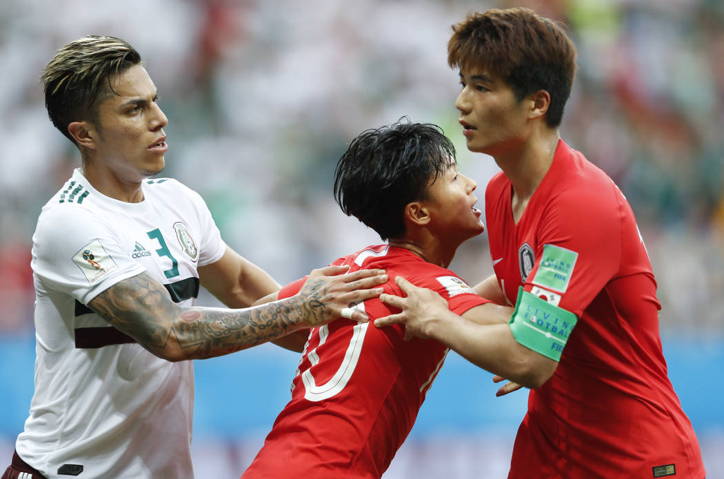 South Korea's Lee Seung-woo, center= hols teammate Ki Sung-yueng as Mexico's Carlos Salcedo stands beside during the group F match between Mexico and South Korea at the 2018 soccer World ...
