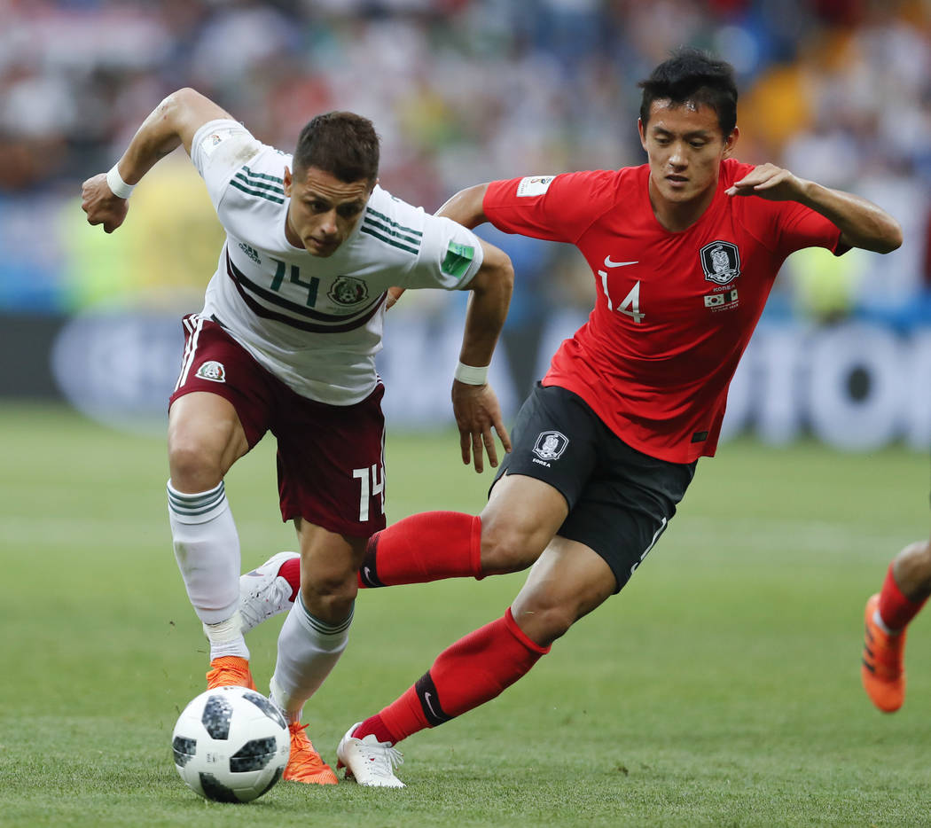 Mexico's Javier Hernandez, left, challenges for the ball with South Korea's Hong Chul during the group F match between Mexico and South Korea at the 2018 soccer World Cup in the Rostov Arena in Ro ...