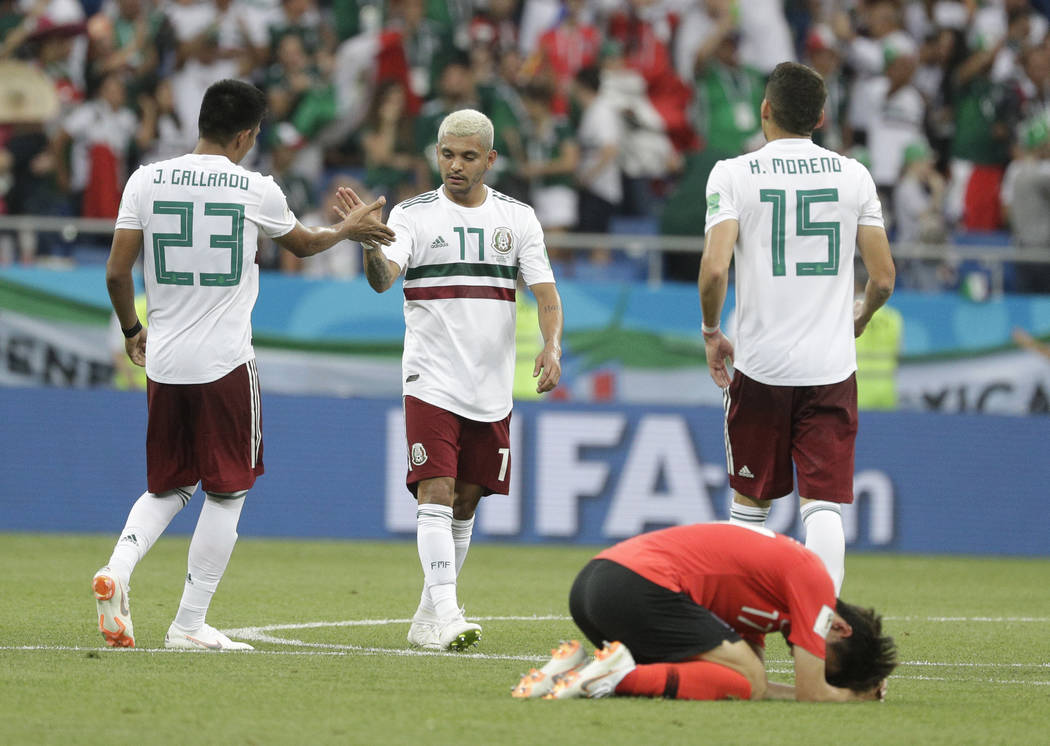 Mexico's Jesus Corona, center, clasps hands with Mexico's Jesus Gallardo as South Korea'sLeeJae-sung lies on the pitch after the group F match between Mexico and South Korea at the 201 ...