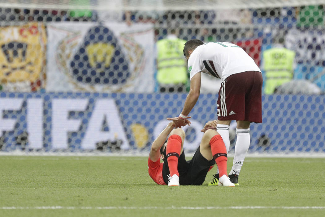 Mexico's Hector Moreno, top, comforts South Korea's Lee Yong during the group F match between Mexico and South Korea at the 2018 soccer World Cup in the Rostov Arena in Rostov-on-Don, Ru ...