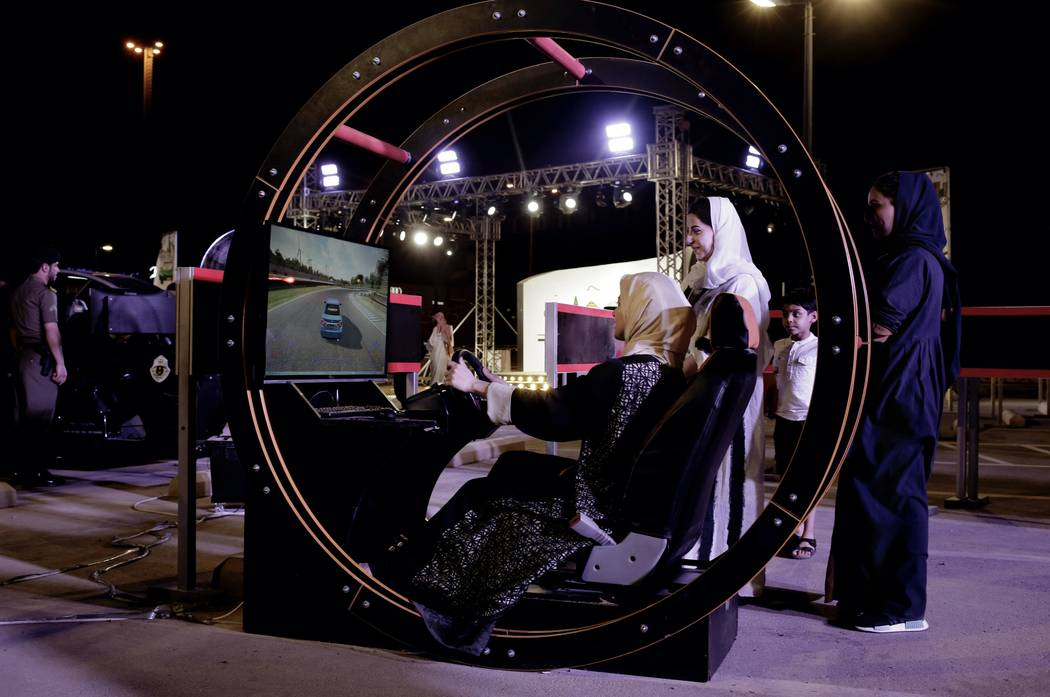 In this June 22, 2018 photo, a woman tests a car driving simulator at a road safety event for female drivers launched at the Riyadh Park Mall in Saudi Arabia. (AP Photo/Nariman El-Mofty)