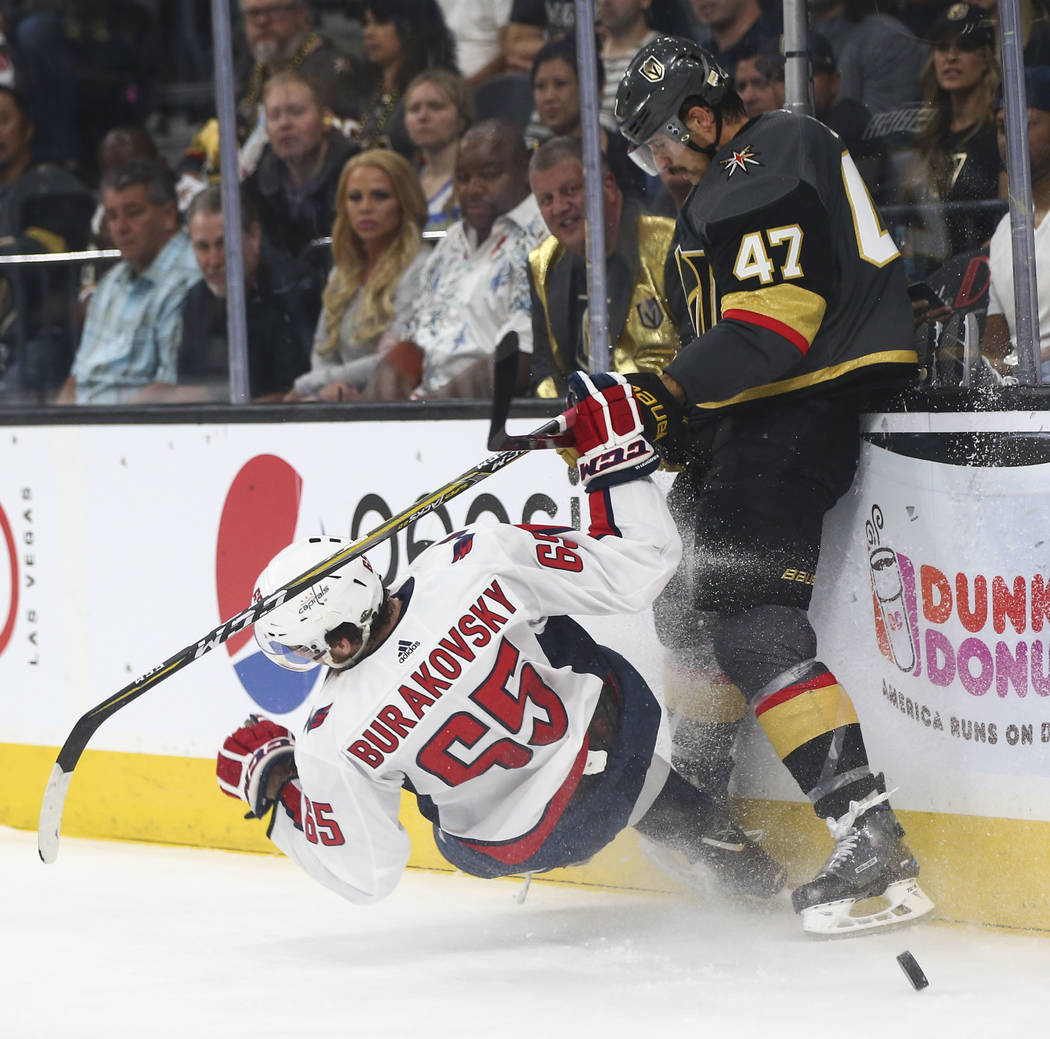 Washington Capitals left wing Andre Burakovsky (65) gets checked by Golden Knights defenseman Luca Sbisa (47) during the second period of Game 1 of the NHL hockey Stanley Cup Final at the T-Mobile ...