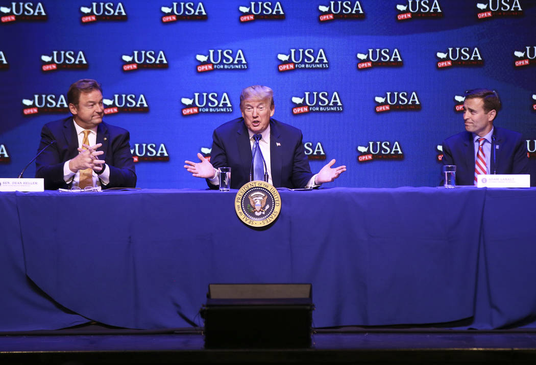 President Donald Trump, center, speaks during a roundtable discussion on tax cuts while flanked by U.S. Sen. Dean Heller, R-Nev., left, and Attorney General Adam Laxalt, Republican candidate for N ...