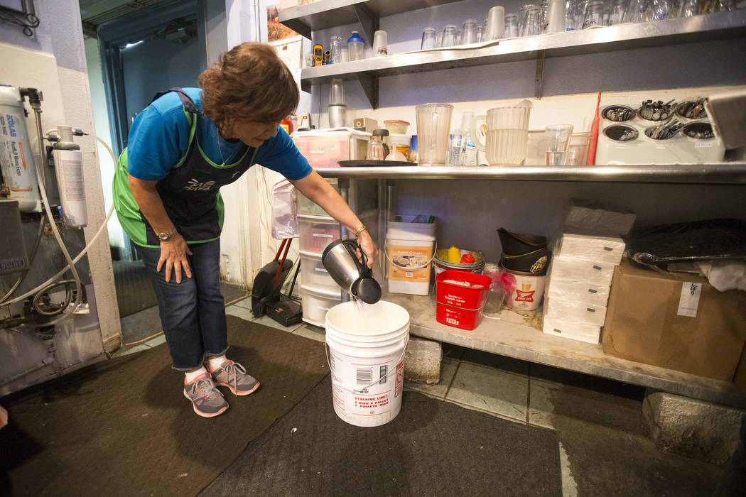 Joan Lee, owner of Minato sushi bar and Korean BBQ, pours hot water into a bucket as she prepares for the lunch crowd at her restaurant in Laughlin on Sunday, June 24, 2018. The Las Vegas Valley W ...