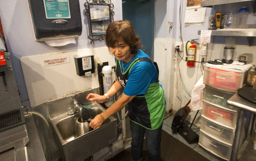 Joan Lee, owner of Minato sushi bar and Korean BBQ, fills tap water into an electric kettle for boiling as she prepares for the lunch crowd at her restaurant in Laughlin on Sunday, June 24, 2018. ...