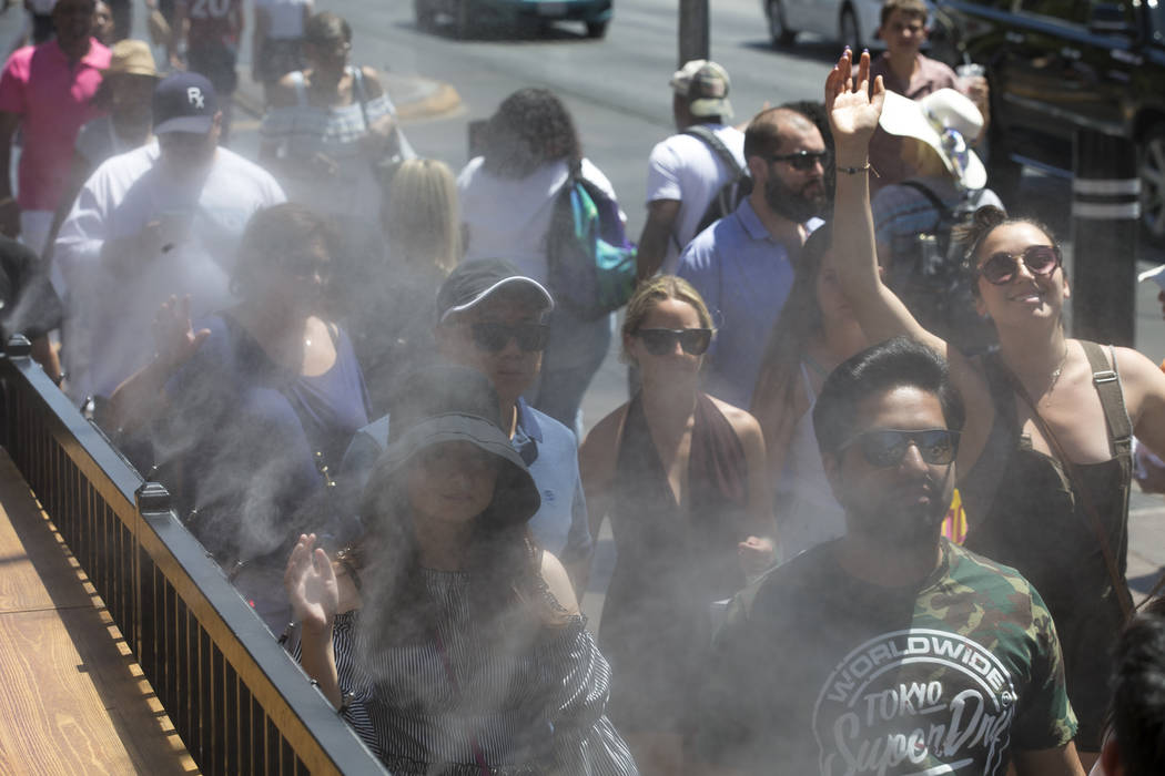 People cool off on a water mister outside the Hexx Kitchen and Bar on the Strip in Las Vegas on Thursday, June 21, 2018. Richard Brian Las Vegas Review-Journal @vegasphotograph