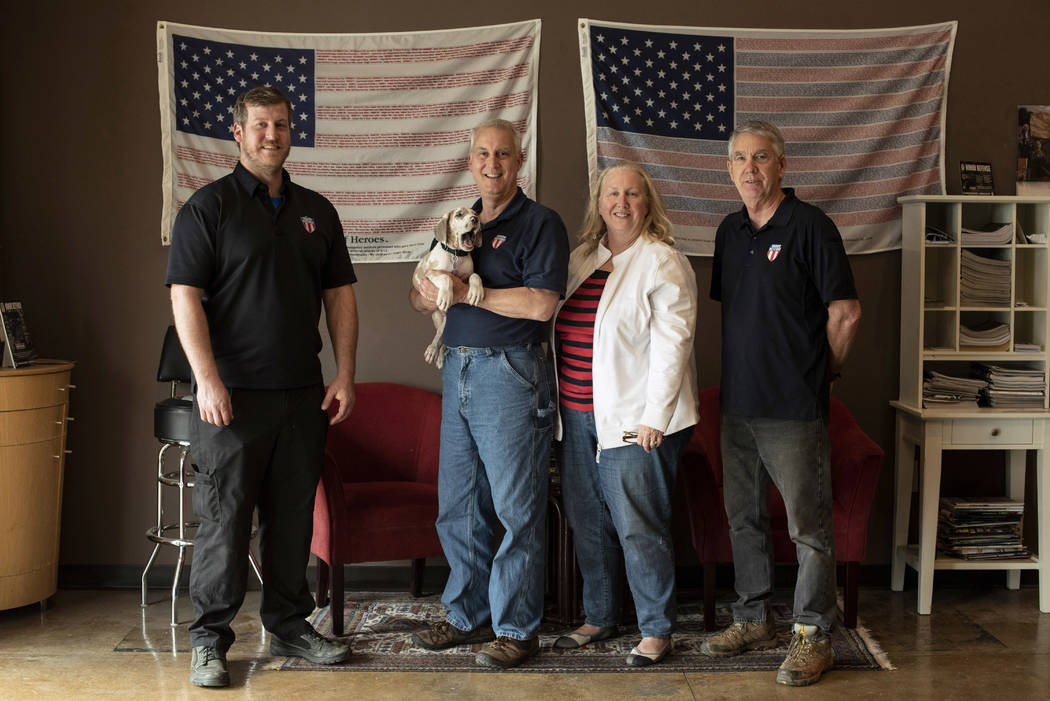 In this April 25, 2018, photo, the owners and employees of Honor Defense, a gunmaker in Gainesville, Ga., pose in the company's lobby. Standing, left to right, are Pete Ramey, who works on the ass ...