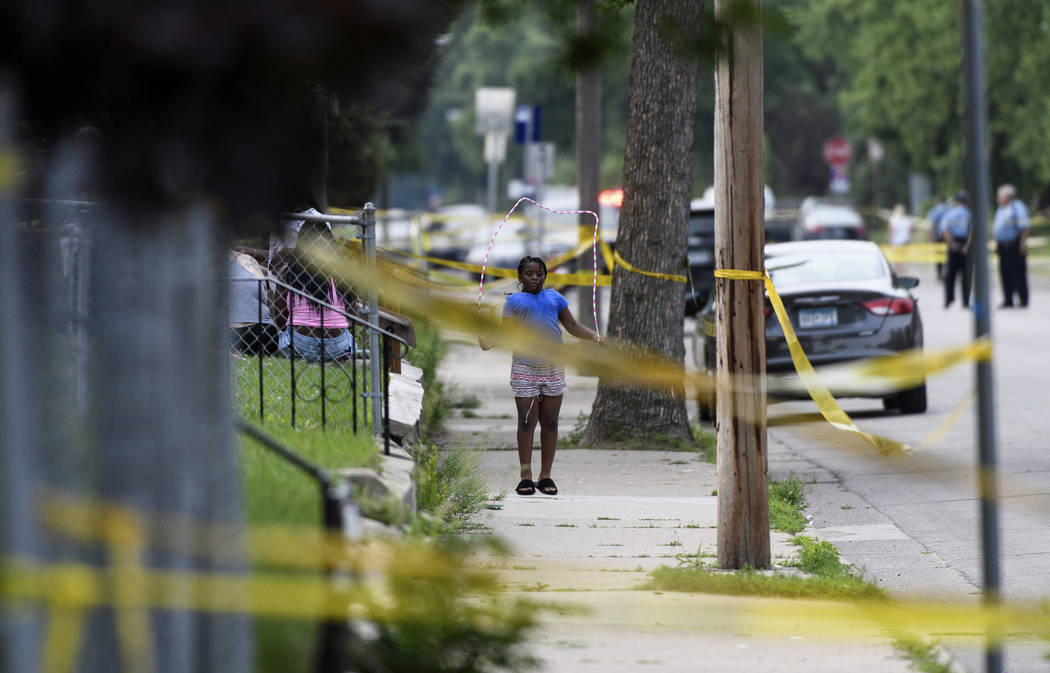 A girl jumps rope outside a home along Bryant Avenue North near the scene of an officer-involved shooting Saturday, June 23, 2018, in Minneapolis. Police in Minneapolis say officers shot and kille ...