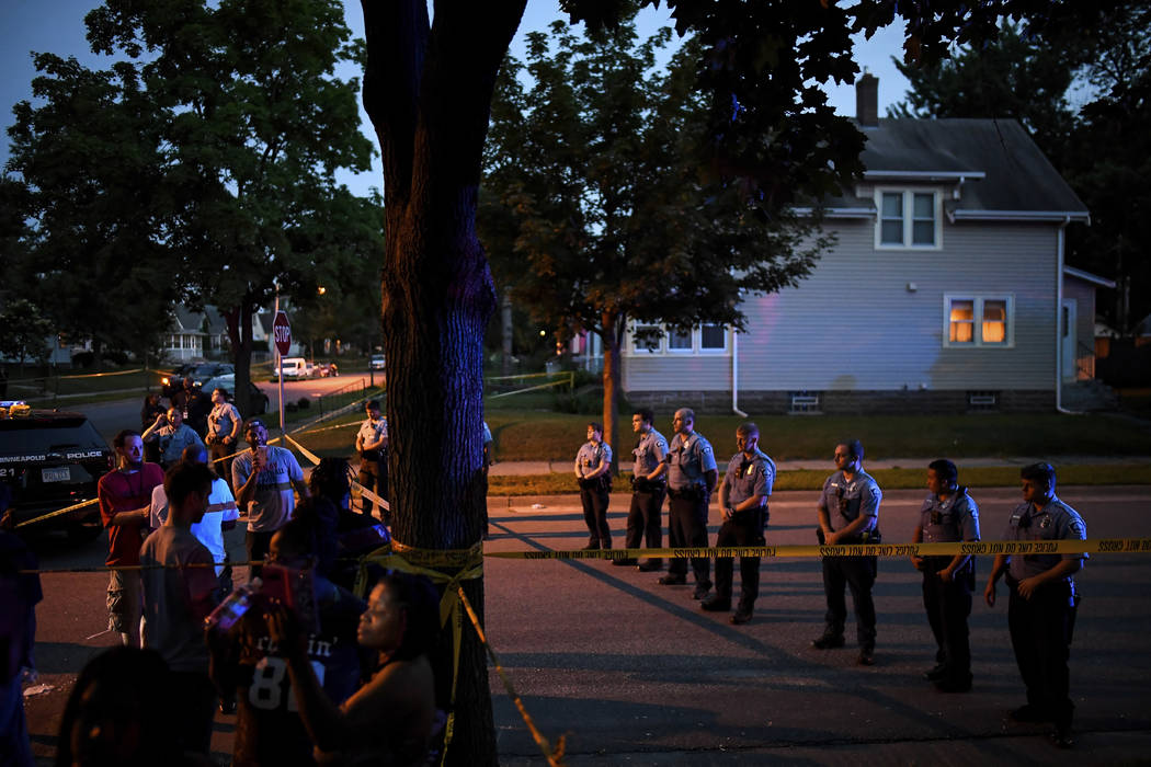 Police form a line in the street as a crowd grew in response to an officer-involved shooting earlier Saturday, June 23, 2018, in Minneapolis. Police in Minneapolis say officers shot and killed a m ...