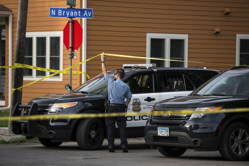 Police investigate the scene of an officer-involved shooting Saturday, June 23, 2018, in Minneapolis. Police in Minneapolis say officers shot and killed a man who was firing a handgun as he walked ...