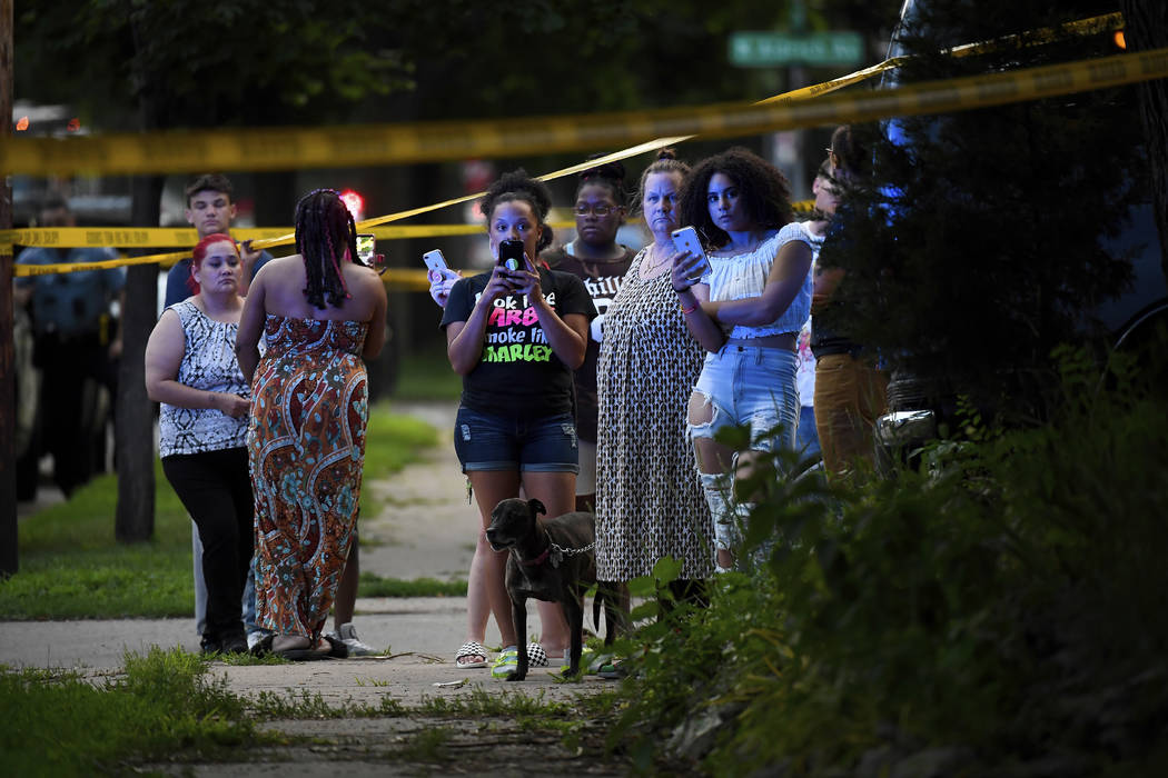 A crowd gathers near the scene of an officer-involved shooting which took place a few hours earlier Saturday, June 23, 2018, in Minneapolis. Police in Minneapolis say officers shot and killed a ma ...