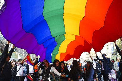 A couple of women take a selfie under a rainbow banner during International LGBT Pride Day in Santiago, Chile, Saturday, June 23, 2018. (AP Photo/Esteban Felix)