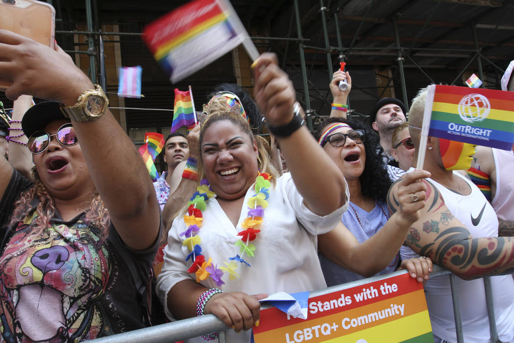 Dayana Pirr, left, and her sister Yoana Pirr, second from left, both visiting from Venezuela, react as they watch the Gay Pride Parade make its way down New York's Seventh Avenue Sunday June 24, 2 ...