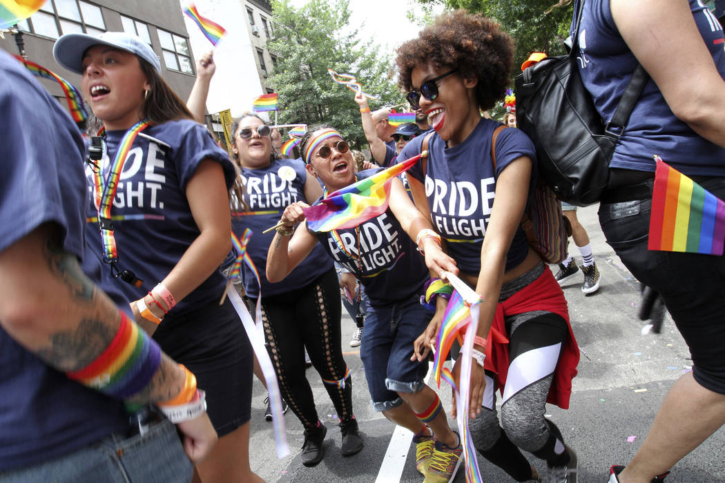 Haydee Lopez, of the Brooklyn borough of New York, center holding flag, dances with others as she takes part in the Gay Pride Parade Sunday June 24, 2018 in New York. (AP Photo/Tina Fineberg)