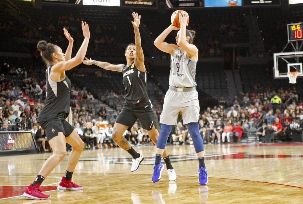 Minnesota Lynx forward Cecilia Zandalasini (9) shoots to make a basket against Las Vegas Aces guard Kayla McBride (5) and forward Tamera Young (1) at a WNBA basketball game at the Mandalay Bay Eve ...