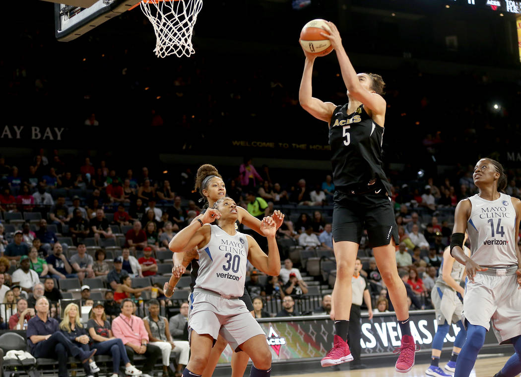 Las Vegas Aces forward Dearica Hamby (5) takes a shot in front of Minnesota Lynx guard Tanisha Wright (30) and center Temi Fagbenle (14) in the first half of a WNBA basketball game at the Mandalay ...
