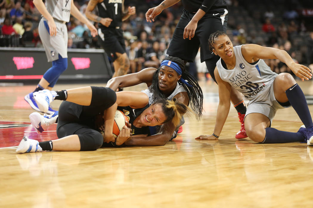 Las Vegas Aces guard Kayla McBride (21) grabs the ball from Minnesota Lynx players center Sylvia Fowles (34) and guard Tanisha Wright (30) at a WNBA basketball at the Mandalay Bay Events Center in ...
