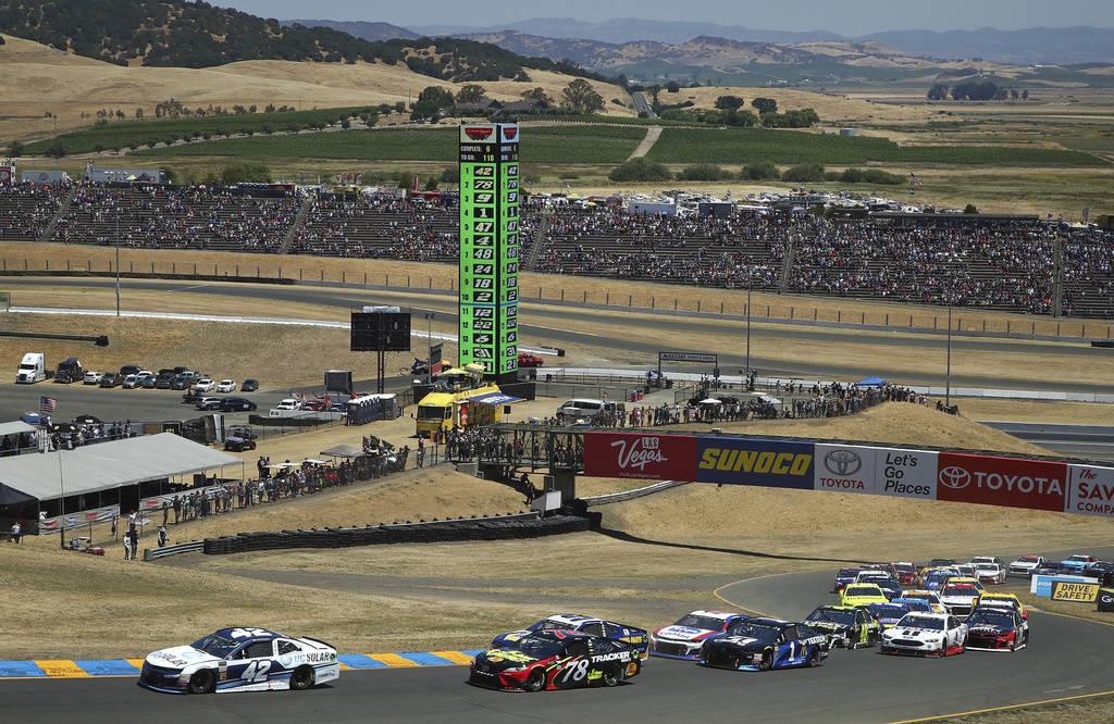 Klye Larson (42) leads Martin Truex Jr. (78) at the start of a NASCAR Sprint Cup Series auto race Sunday, June 24, 2018, in Sonoma, Calif. (AP Photo/Ben Margot)