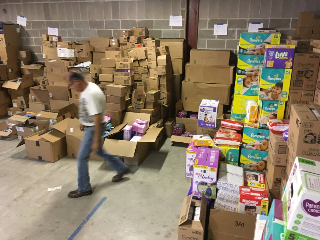 In this photograph taken June 24, 2018, Catholic Charities of the Rio Grande Valley staffer Eli Fernandez walks by boxes of donations at a storage facility in McAllen, Texas. A rest center for asy ...