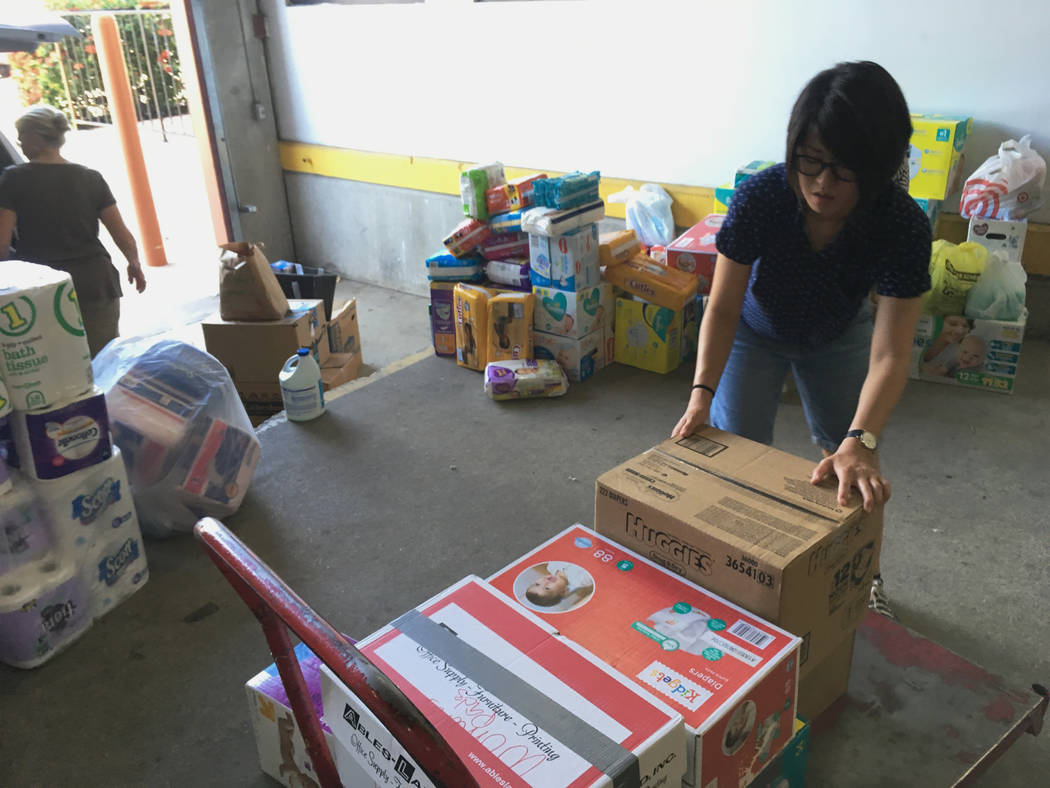 In this photograph taken June 24, 2018, Catholic Charities of the Rio Grande Valley volunteer Veronica Yoo loads boxes of donations on to a cart at a storage facility in McAllen, Texas. The respit ...