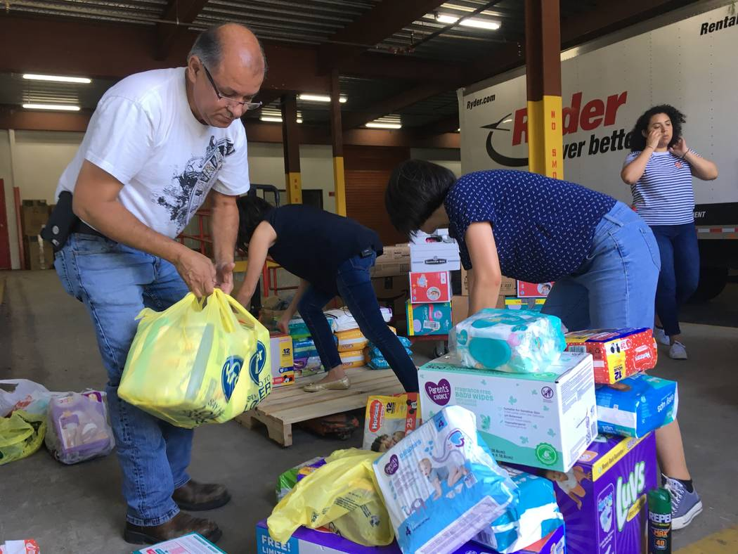 In this photograph taken June 24, 2018, a Catholic Charities of Rio Grande Valley staffer and volunteers unload boxes of donations on to a cart at a storage facility in McAllen, Texas. A rest cent ...