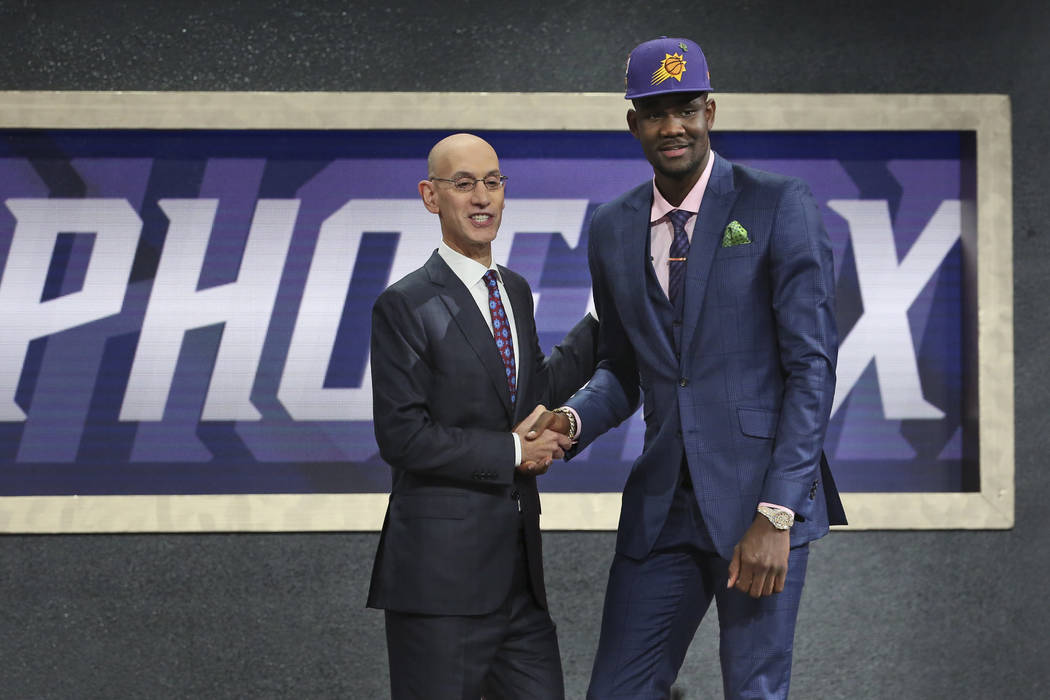 Arizona's Deandre Ayton, right, poses with NBA Commissioner Adam Silver after he was picked first overall by the Phoenix Suns during the NBA basketball draft in New York, Thursday, June 21, 2018. ...