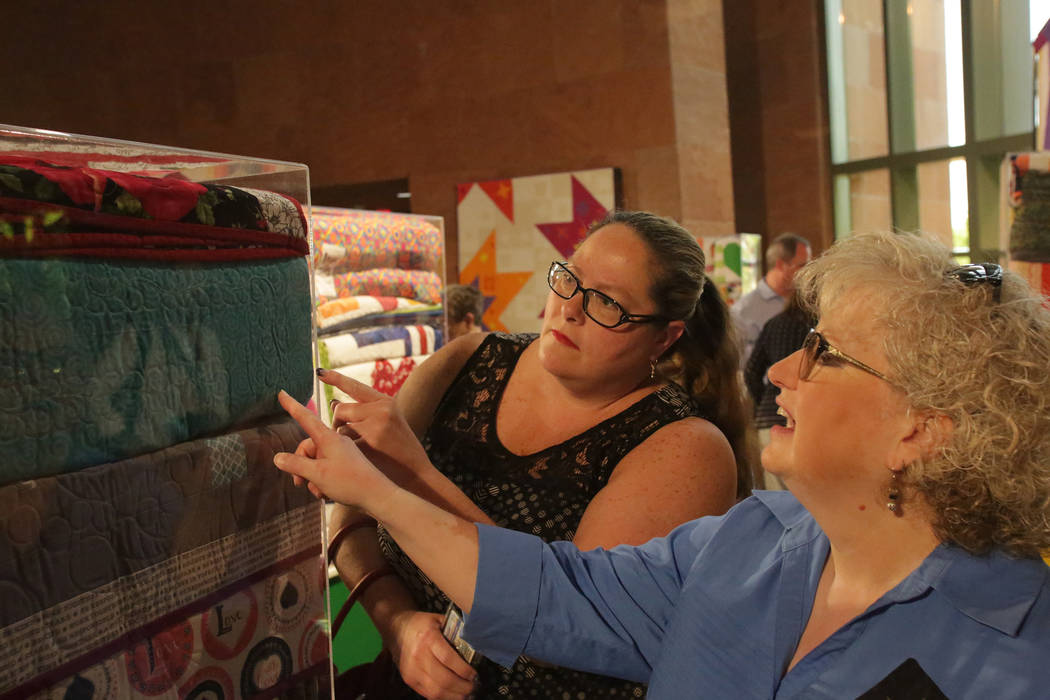 Modern Quilting Guild members Sherri Still, left and Gina Fiddes admire some of the 250 quilts donated to the Vegas Strong Resiliency Center to help victims of the Oct. 1 shooting in Las Vegas at ...
