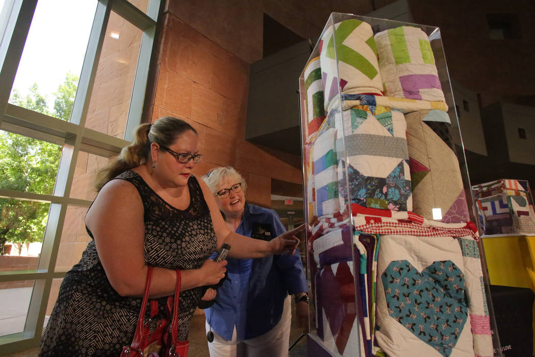 Modern Quilting Guild members Sherri Still, left, and Gina Fiddes admire some of the 250 quilts donated as they look for ones that they contributed to the Vegas Strong Resiliency Center to help vi ...