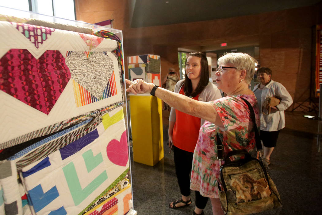 During an exhibit at the Clark County Government Center on Monday, June 25, 2018, Kathy Farris, right, points out details to Modern Quilting Guild member Sara Carey in one of the over 250 quilts t ...