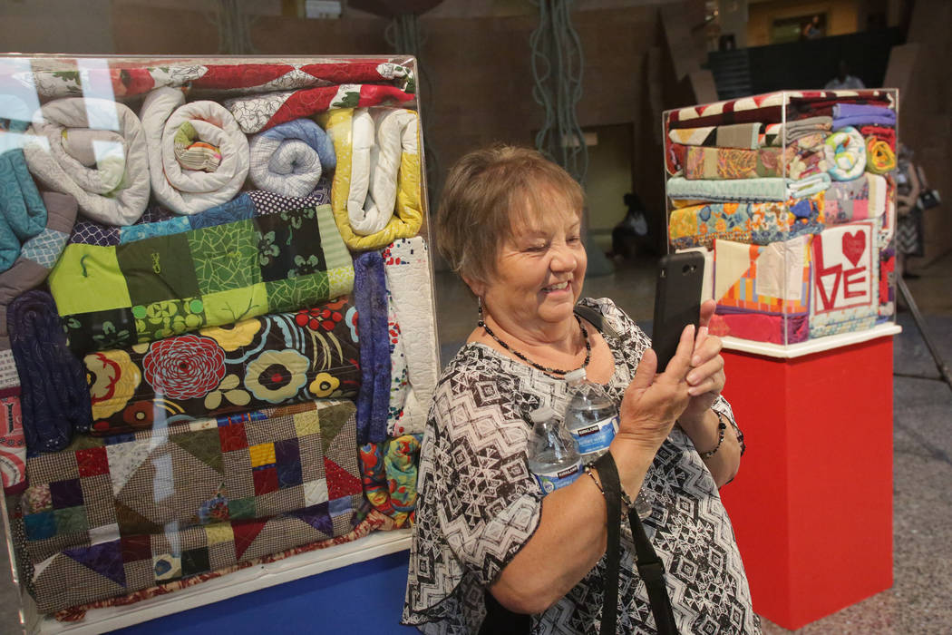 Pam Zeller of Montgomery, Texas, grabs a picture of one of the quilts her sister, Gina Fiddes, contributed to the over 250 quilts that were donated to the Vegas Strong Resiliency Center to help vi ...