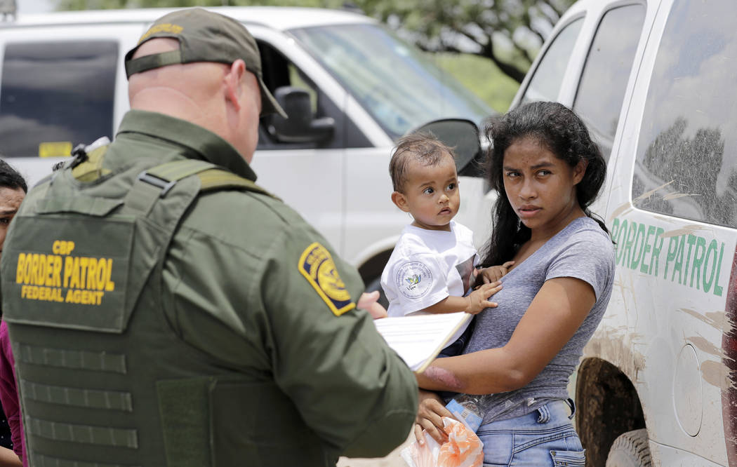 A mother migrating from Honduras holds her 1-year-old child while surrendering to U.S. Border Patrol agents after illegally crossing the border Monday, June 25, 2018, near McAllen, Texas. (AP Phot ...