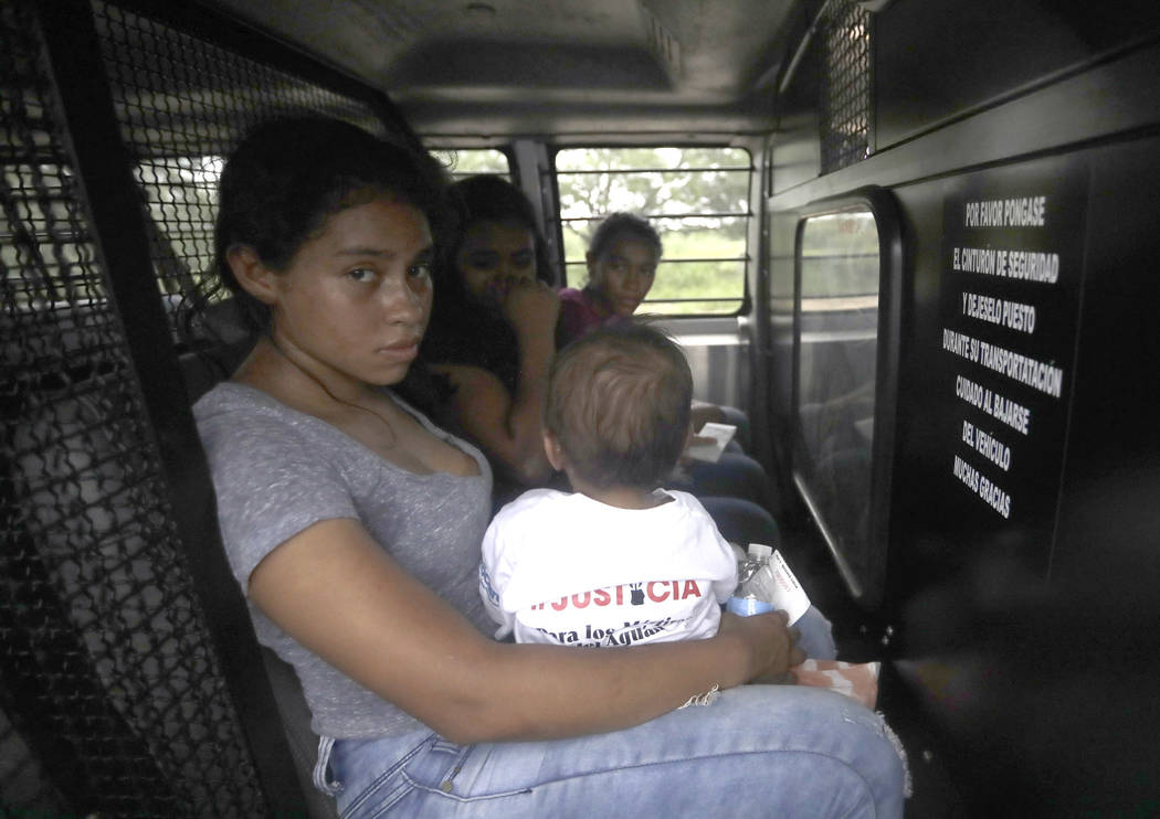 A mother migrating from Honduras holds her one-year-old child in the back of a transport van after surrendering to U.S. Border Patrol agents Monday, June 25, 2018, near McAllen, Texas. They are pa ...