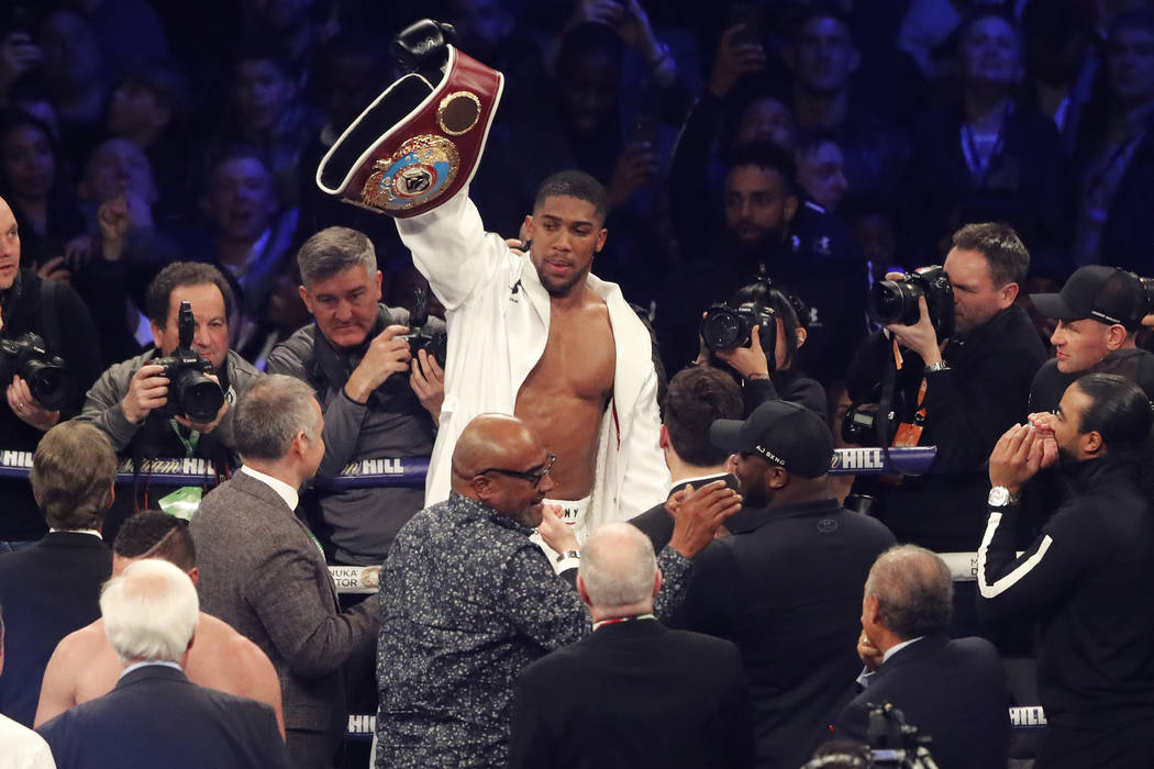 In this file photo dated Saturday, March 31, 2018, Britain's Anthony Joshua celebrates after his WBA, IBF, WBO and IBO Heavyweight Championship title bout against New Zealand's Joseph Parker in Ca ...