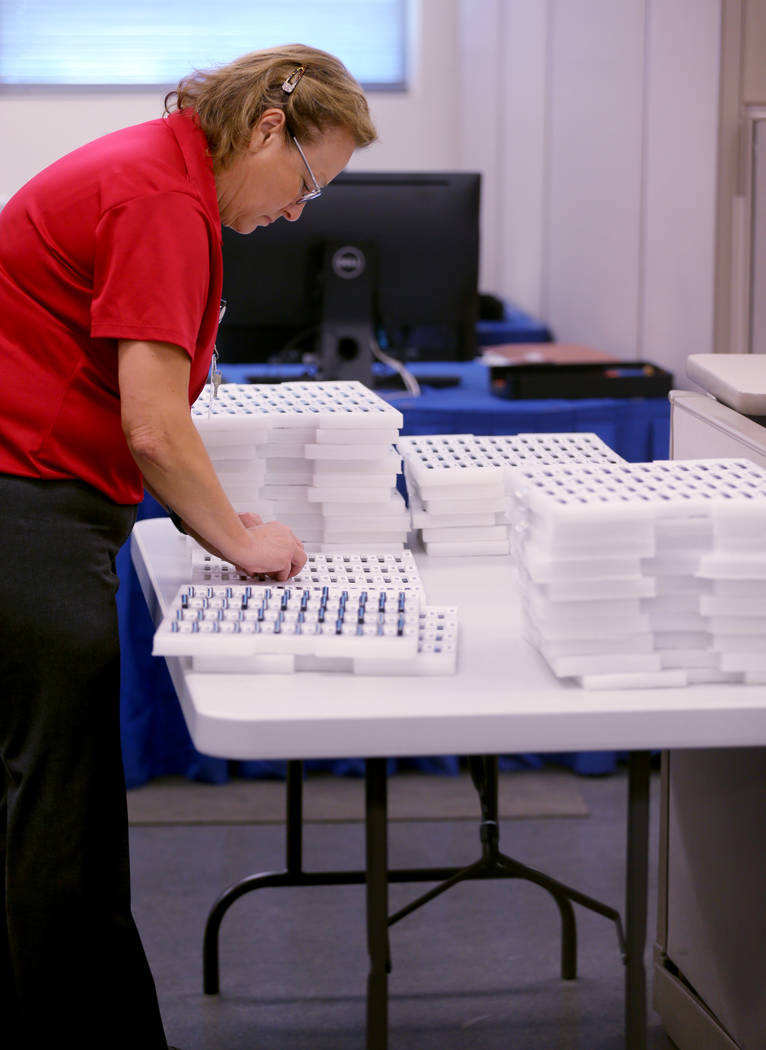 A Clark County election worker loads voting machine results cartridges during a recount of the Democratic primary for the County Commission District E seat at election headquarters in Las Vegas Tu ...