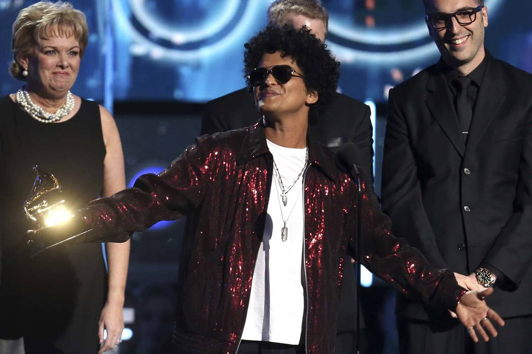 """Bruno Mars accepts the award for record of the year for """"24K Magic"""" at the 60th annual Grammy Awards in New York, Jan. 28, 2018. The Grammy Awards are extending the number of nominees in its top c ..."""