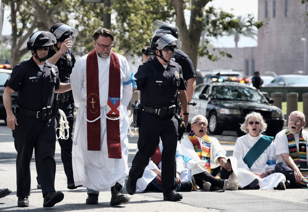 A clergy member is arrested during a civil disobedience protest in front of Federal Courthouse in Los Angeles on Tuesday, June 26, 2018. Immigrant-rights advocates asked a federal judge to order ...