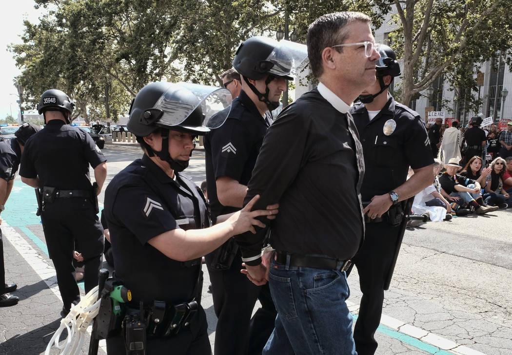 A member of clergy group is arrested during a protest in front of Federal Courthouse in Los Angeles on Tuesday, June 26, 2018. Immigrant-rights advocates asked a federal judge to order the release ...